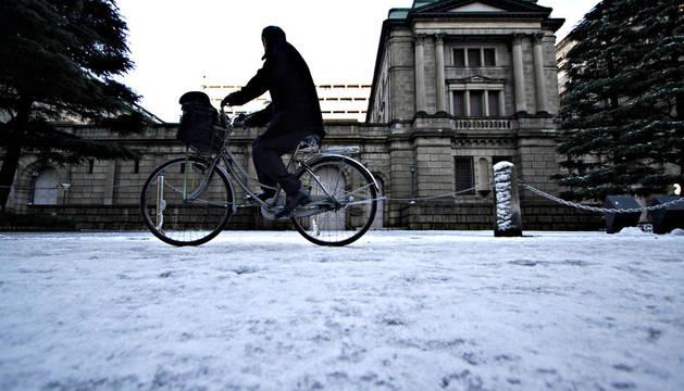 Un hombre pasea en bicicleta ante la sede del Banco de Japón en la capital nipona, Tokyo