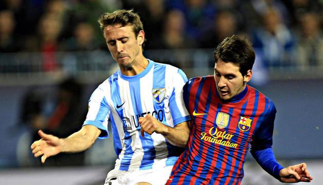 El lateral navarro Nacho Monreal (izda.) pugna con el delantero del FC Barcelona, el argentino Lionel Messi, durante un encuentro disputado en La Rosaleda