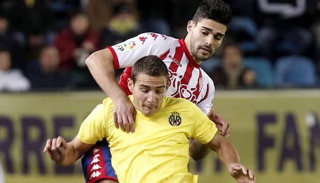 El delantero argentino del Villarreal Marco Ruben pelea un balón con el defensa del Sporting de Gijón Alberto Botía (detrás), durante el partido.