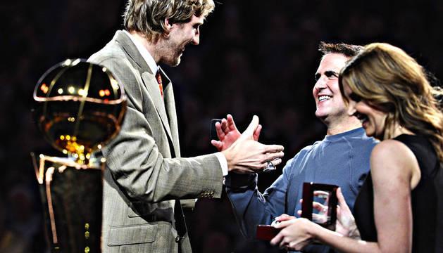 El jugador de los Mavericks Dirk Nowitzki saluda al dueño del equipo, Mark Cuban (centro), tras recibir el anillo del Campeonato de la NBA antes del partido ante los Timberwolves en el American Airlines Center de Dallas, Texas