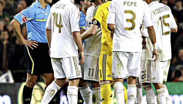 Los jugadores del Real Madrid protestan al árbitro, Fernando Teixeira (izda.), tras el partido de vuelta de los cuartos de final de la Copa del Rey que jugaron contra el FC Barcelona