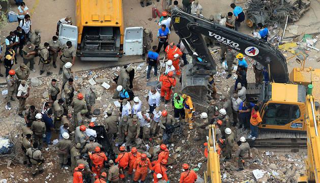 Bomberos y equipos de rescate recuperan un cuerpo de entre los escombros de uno de los edificios que se desplomaron en el centro de Río de Janeiro (Brasil)