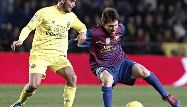 El delantero del FC Barcelona, Leo Messi (d), intenta zafarse del defensa del Villarreal, Joan Oriol, durante el partido correspondiente a la vigésimo primera jornada del Campeonato Nacional de Liga de Primera División.