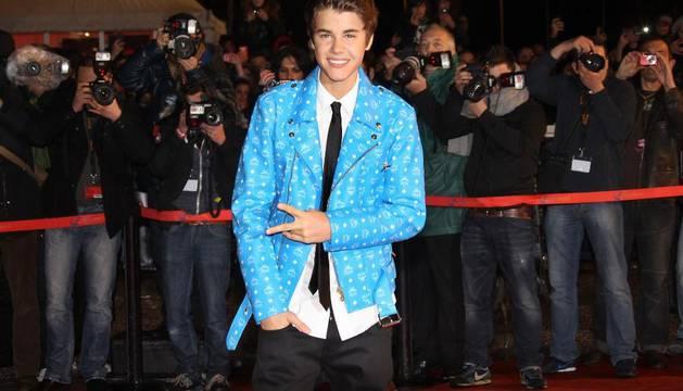El cantante Justin Bieber posa ante las cámaras con su nuevo look