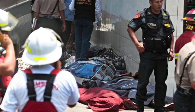 Los policías custodian varios cadáveres junto al centro donde se produjo el incendio