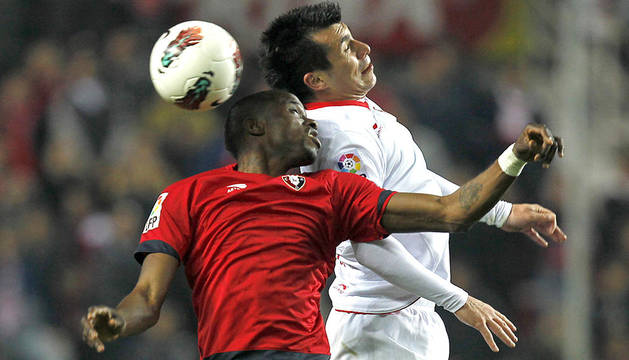 Roland Lamah (izda.) que saltó en el segundo tiempo pugna con el chileno Gary Medel (dcha.) en un momento del partido entre Sevilla y Osasuna disputado en el estadio Sánchez Pizjuán