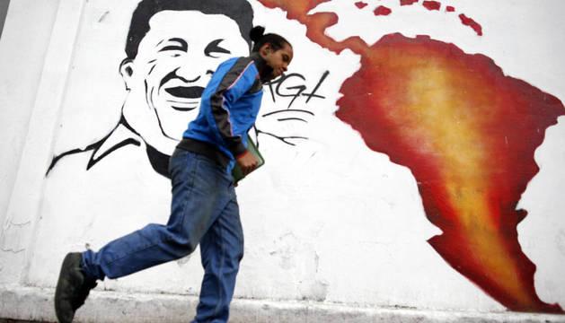 Un hombre camina frente a un mural alusivo al presidente venezolano, Hugo Chávez, en una calle de Caracas.