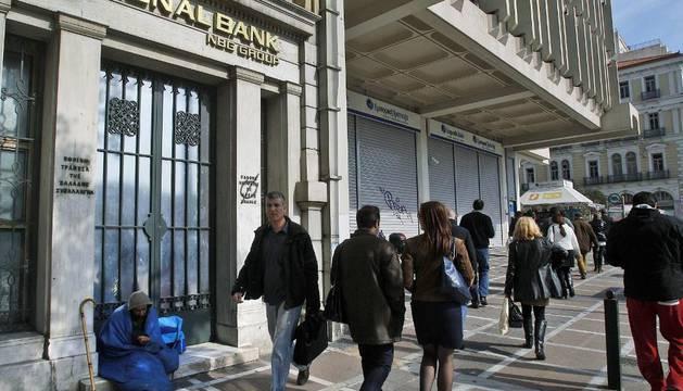 Varias personas caminan junto a una oficina del Banco Nacional de Grecia, en Atenas