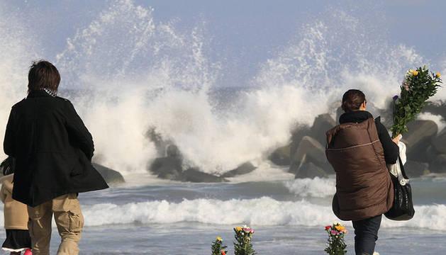 Varias personas dejan flores en la playa durante el primer aniversario del terremoto de 9 grados Richter y el devastador tsunami que arrasó el noreste de Japón,