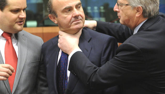 El presidente del Eurogrupo Jean-Claude Juncker (dcha.) bromea con el ministro español de Economía, Luís de Guindos (centro) ante la mirada del ministro holandés de Finanzas Jan Kees (izda.) al comienzo de la reunión del Eurogrupo