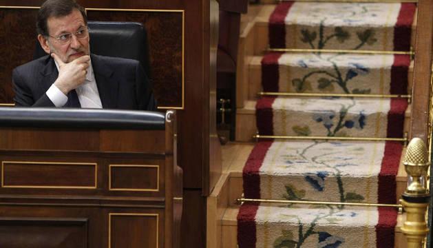 El presidente del Gobierno, Mariano Rajoy, escucha las intervenciones de los portavoces de los diferentes grupos parlamentarios, tras su comparecencia ante el pleno del Congreso.