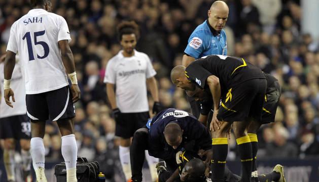 El árbitro Howard Webb mira al centrocampista del Bolton Fabrice Muamba mientras es tratado por los servicios médicos, tras desvanecerse en el campo durante el partido frente al Tottenham.