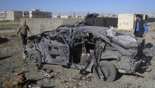 Iraquíes junto a los restos calcinados de un coche