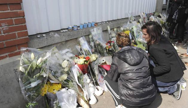 nas personas depositan flores en el exterior del colegio judío