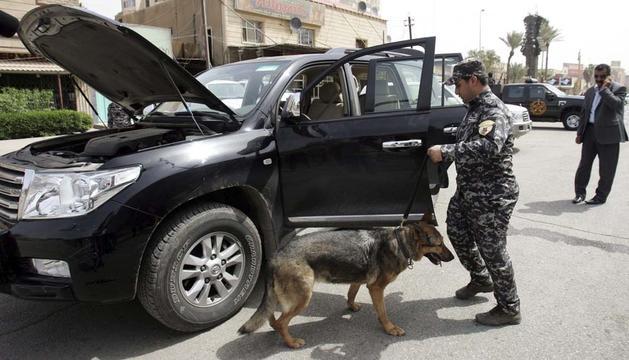 Un policía y su perro registran un vehículo en un control en Bagdad ante el inicio de la Cumbre de la Liga Árabe