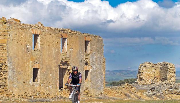 Un ciclista paseando entre las ruinas que quedan en pie del antiguo poblado de Baigorri, entre Oteiza, Lerín y Allo