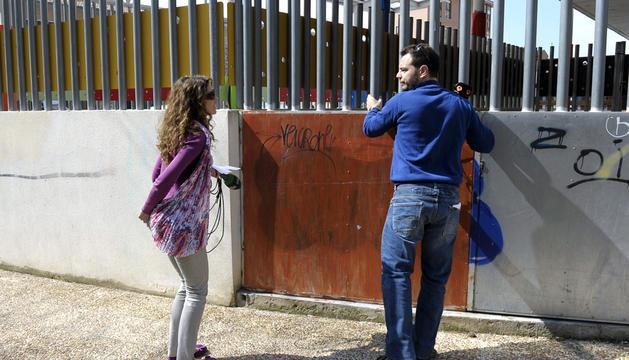 Dos periodistas permanecen junto a la guardería de Tafalla (Navarra) en la que ocurrió el accidente que ha costado la vida a un menor, y que ha reanudado  su actividad entre la conmoción y el dolor
