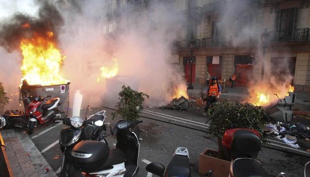 Contenedores incendiados en las calles de Barcelona, durante la manifestacion antisistema en la jornada de huelga general