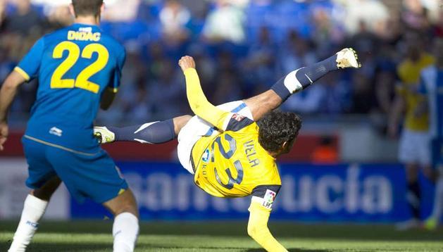 El delantero mexicano de la Real Sociedad, Carlos Vela (d), intenta un remate de chilena en presencia del defensa del Espanyol Didac Vilá