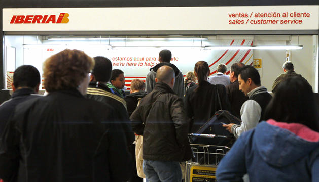 Pasajeros afectados consultan en uno de los mostradores de atención al cliente de Iberia en la T4