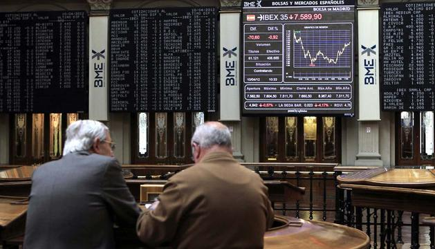Dos inversores asiduos al palacio de la Bolsa de Madrid conversan este martes frente a uno de los paneles informativos del parqué