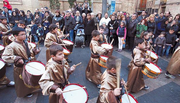 Un grupo de niños de la banda de tambores hace sonar sus instrumentos durante la procesión.
