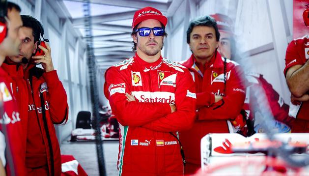 El piloto español de Fórmula Uno de la escudería Ferrari, Fernando Alonso (centro), permanece en el garage del equipo durante la tercera y última sesión de entrenamientos libres para el Gran Premio de China que se disputa en Shanghái