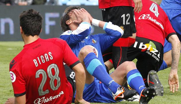 El defensa del Getafe CF Juan Valera (centro) se lamenta de una ocasión de gol fallada en presencia del lateral del RCD Mallorca Pedro Bigas (izda.)