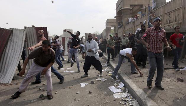 Unos manifestantes lanzan piedras a unos militares cerca del Ministerio de Defensa, en El Cairo.