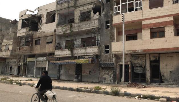 Un hombre pasea con su bicicleta junto a un edifico dañado en Homs