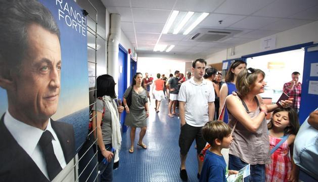 Ciudadanos franceses esperan para entrar a votar durante la segunda y definitiva vuelta de los comicios presidenciales galos, en un colegio francés de Hong Kong
