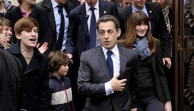 El candidato conservador a la presidencia de Francia, Nicolas Sarkozy (c), y su esposa Carla Bruni-Sarkozy (dcha) salen del Liceo Jean de la Fontaine