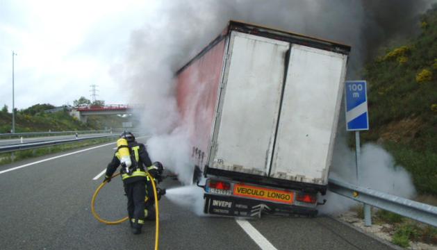 Los bomberos sofocan el fuego en la parte trasera del camión