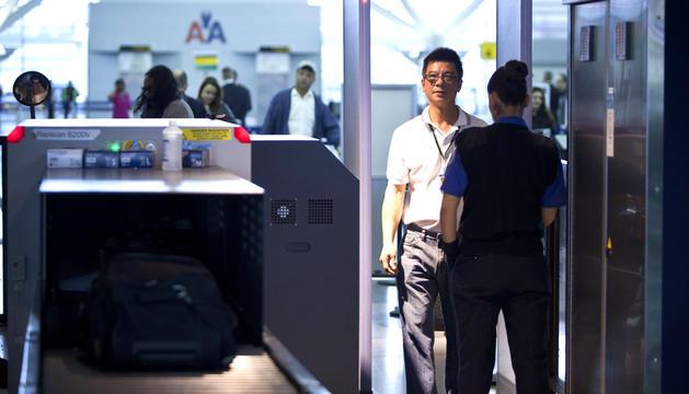 Un pasajero es registrado por un agente de seguridad en el aeropuerto John F. Kennedy de Nueva York