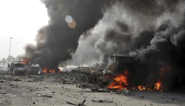Imagen distribuida por la agencia de noticias siria SANA que muestra varios coches envueltos en llamas tras el doble atentado perpetrado en la zona de Qazaz, a unos cinco kilómetros al sur de Damasco