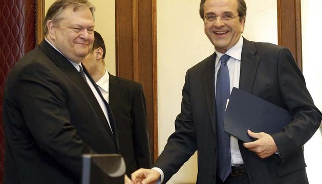 El líder socialista Evangelos Venizelos (izda) estrecha la mano del líder del conservador partido Nueva Democracia (ND), Antonis Samaras (dcha)