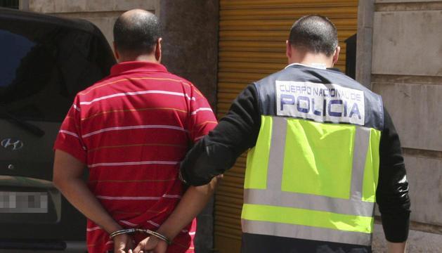 Un policía, con uno de los ocho detenidos