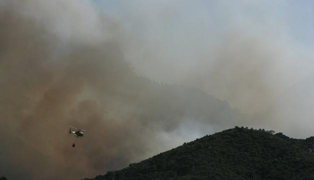 Los bomberos continúan trabajando para extinguir el incendio de la Rasquera (Tarragona).