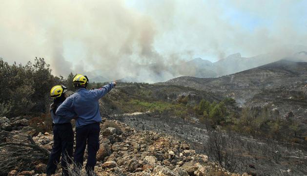Dos bomberos observan los efectos del incendio