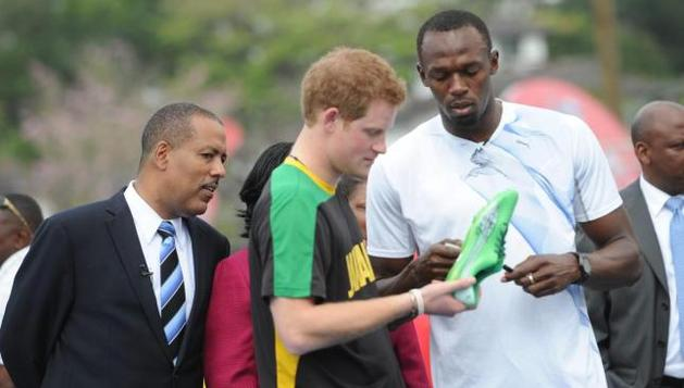 El príncipe Enrique de Inglaterra (c), dialoga con el atleta jamaiquino Usain Bolt (d), durante su visita oficial a Kingston (Jamaica)
