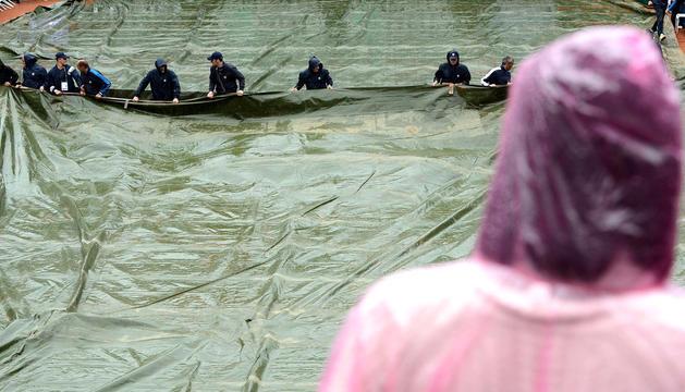 Momento en el que los empleados tapan con una lona la pista de Roma por la lluvia, que ha suspendido la final femenina y ha aplazado la masculina
