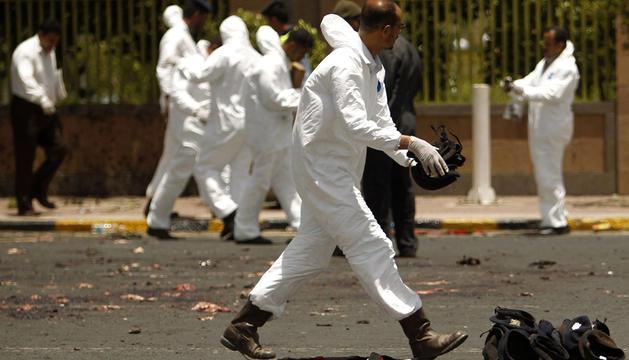 Un policía forense recoge los cacos de los militares muertos en el lugar donde tuvo lugar el atentado suicida que se cobró la vida de 70 personas en la ciudad de Saná.