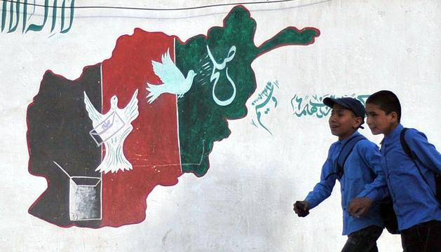 Dos escolares afganos pasan junto a un mural con los colores de la bandera del país