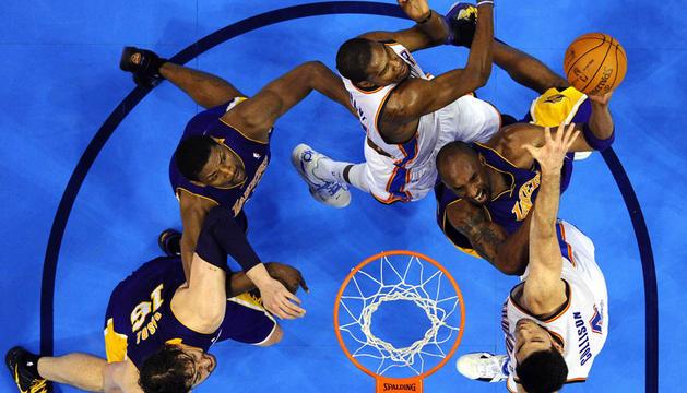 El jugador de Lakers Kobe Bryant (2d) disputa el balón con Kevin Durant (3d) y Nick Collison (d) de Thunder