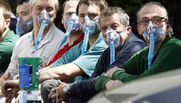 Un grupo de trabajadores de Kybse inhalan oxígeno a través de una mascarilla
