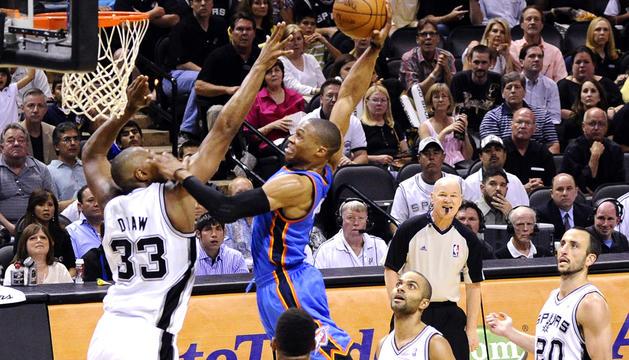 El jugador de los Spurs de San Antonio Boris Diaw (izda.) trata de frenar la entrada a canasta de Russell Westbrook (centro) de los Thunder de Oklahoma City