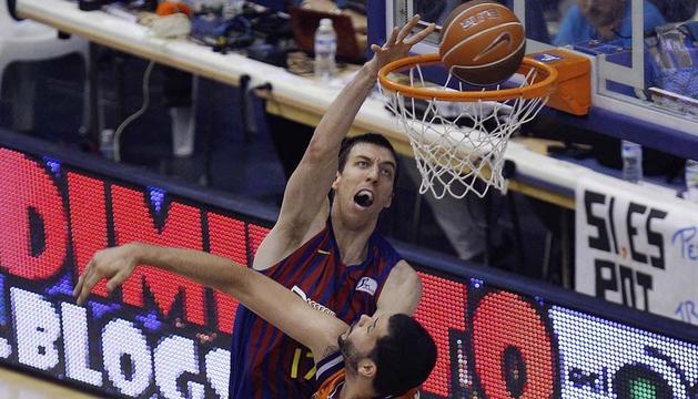 El pívot del Barcelona Regal, Fran Vazquez (i), encesta ante la oposición del pívot brasileño del Valencia Basket, Vitor Faverani,