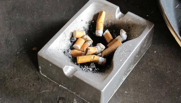 Un cenicero con colillas de cigarros