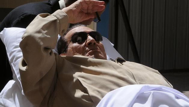 El expresidente egipcio, Hosni Mubarak, mientras le trasladan fuera de los tribunales