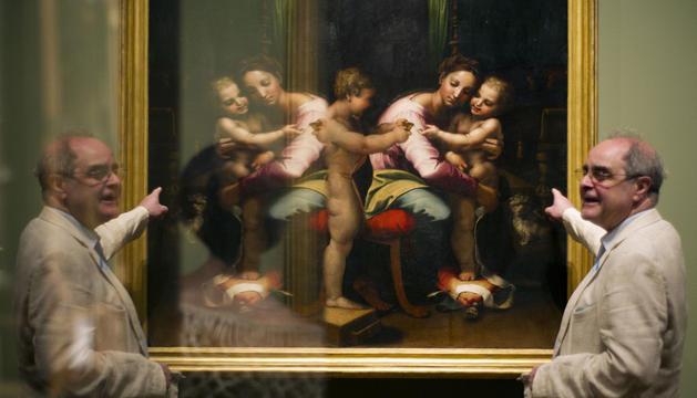 Un hombre junto a uno de los cuadros de la exposición de Rafael